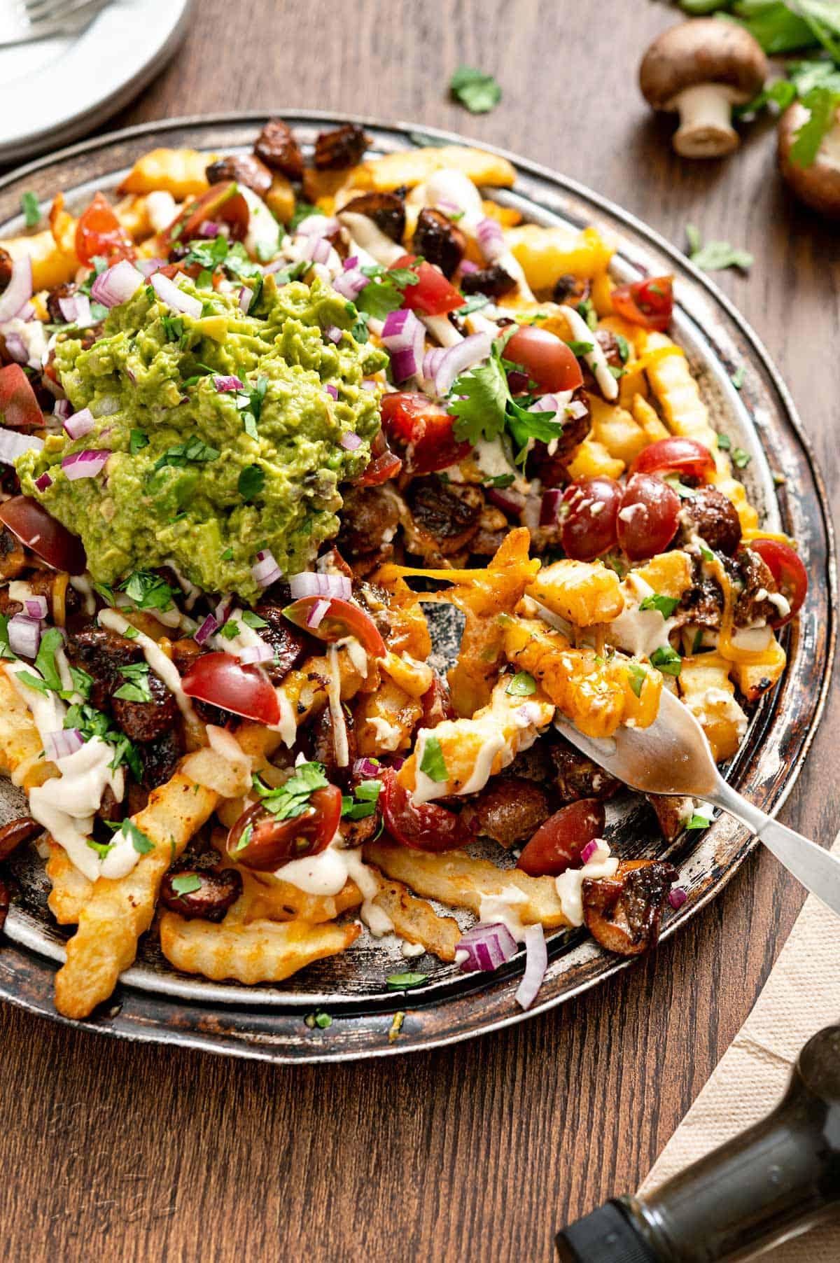 Close up shot of a platter of vegan mushroom asado fries on a wood table