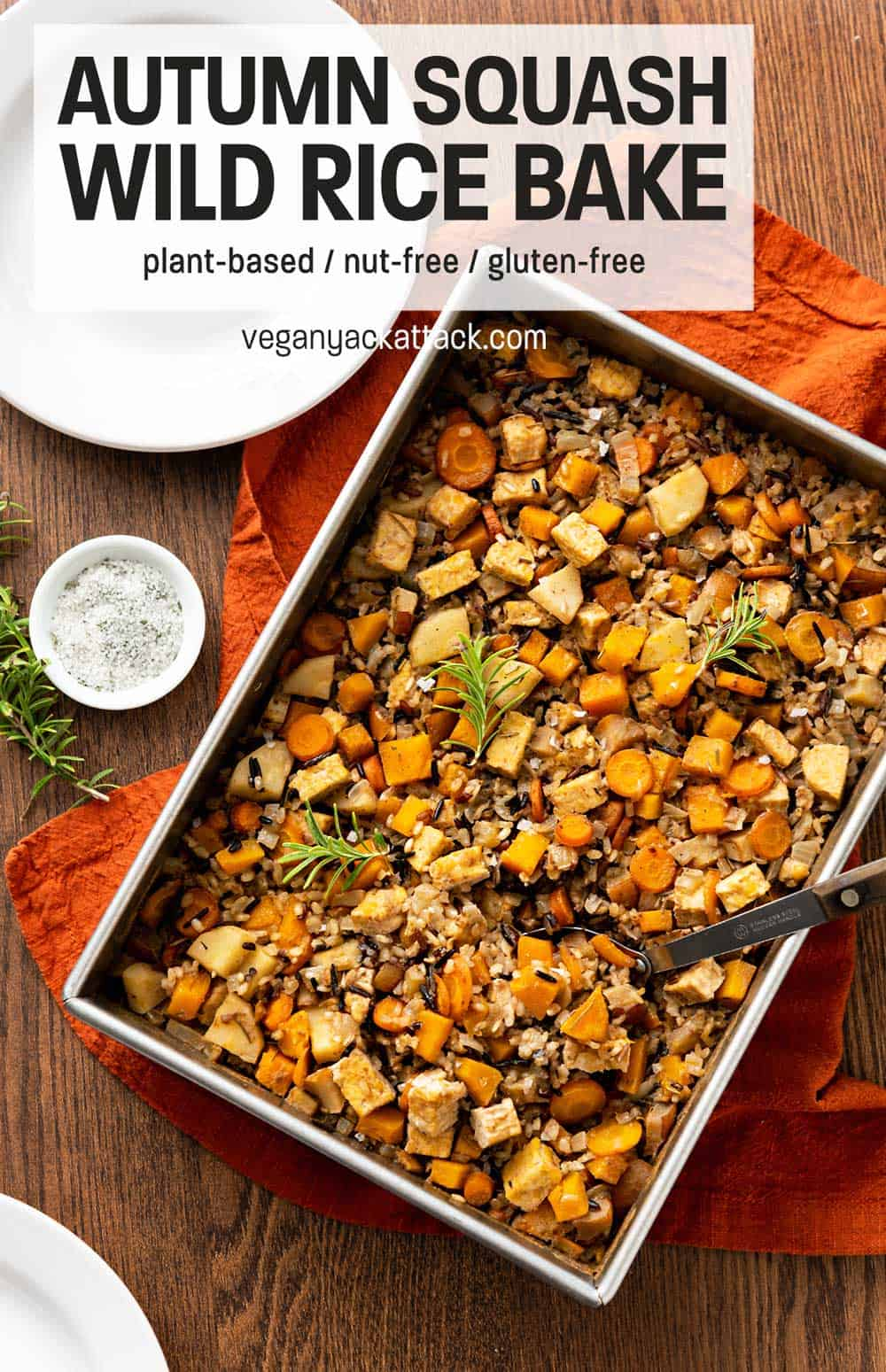 Large baking pan of squash wild rice bake on a brown wood table with rust-colored linen