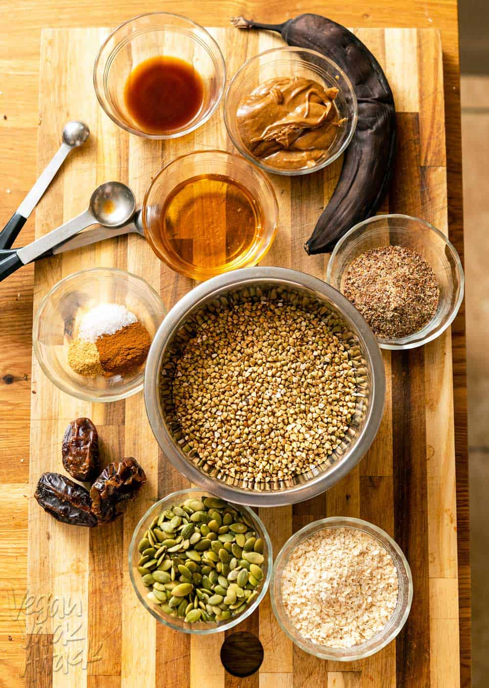 Buckwheat, banana, pepitas, dates, and other ingredients laid out on a cutting board