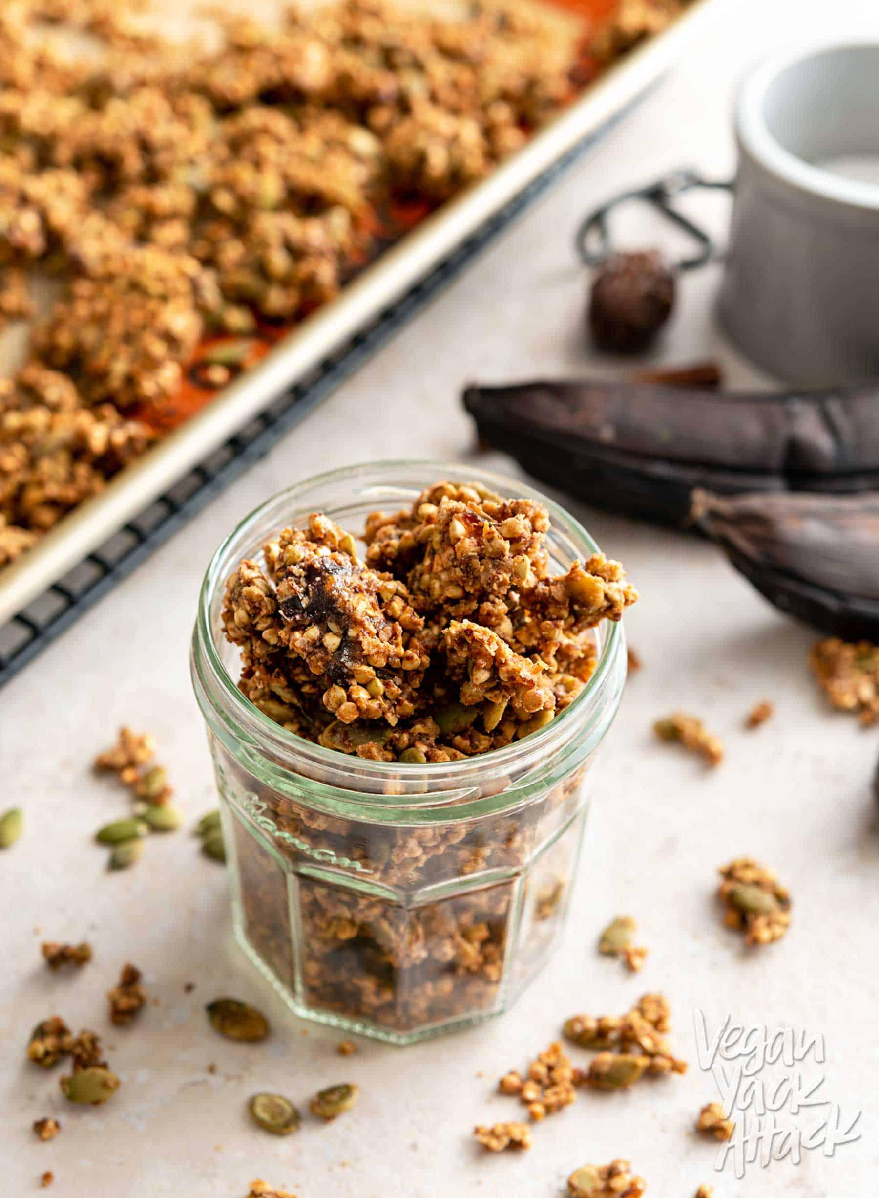Jar of buckwheat granola next to ripe bananas and baking sheet