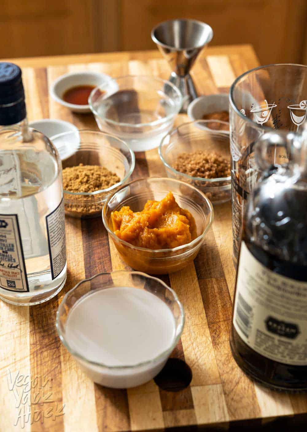 Pumpkin, sugar, cookie crumbs, and more in ramekins on a cutting board