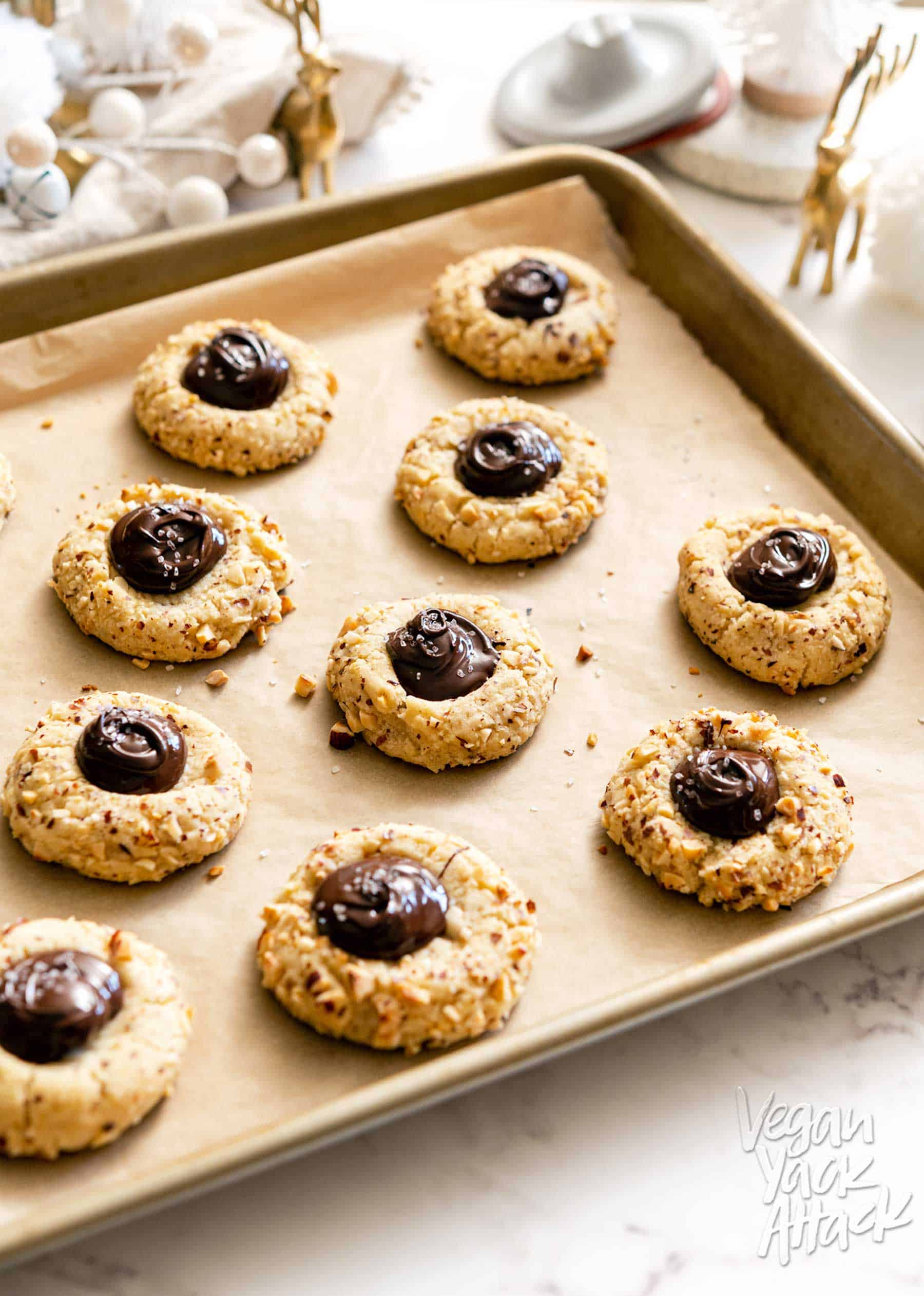Sheet pan filled with chocolate hazelnut thumbprint cookies, and various Christmas decor