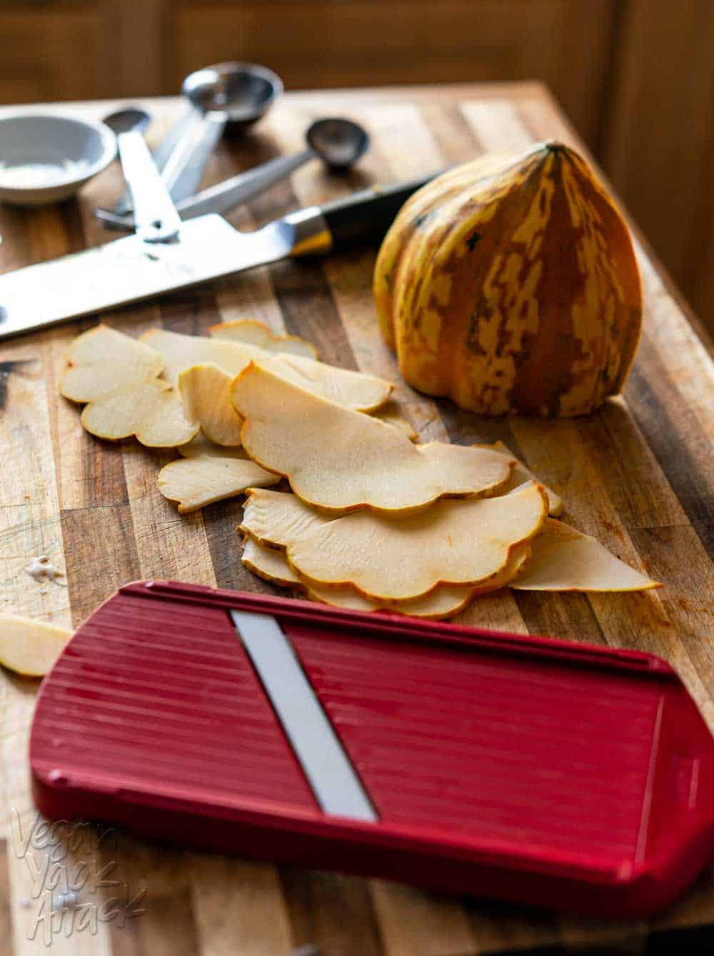 Thinly sliced acorn squash next to a red mandolin