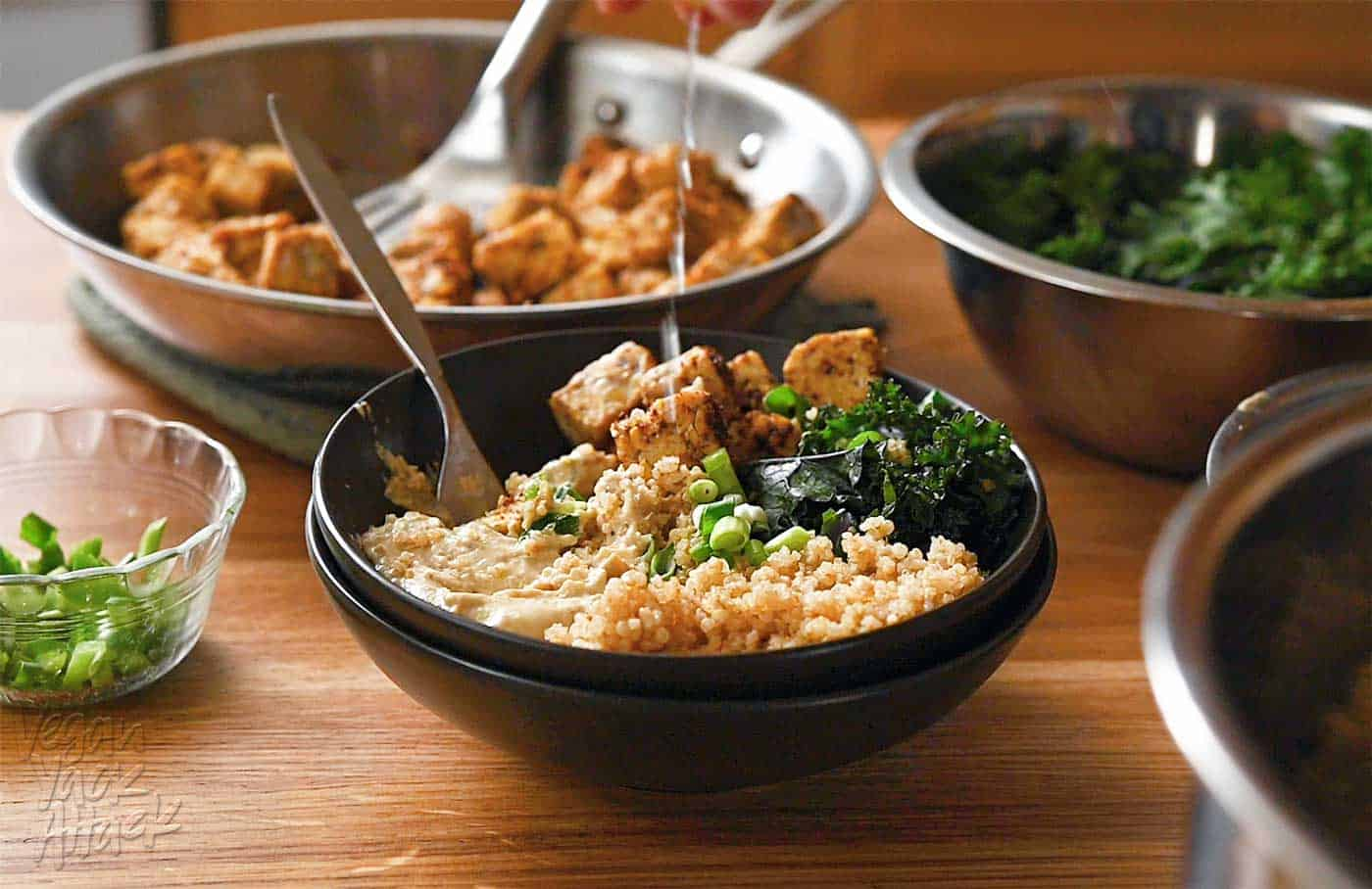 Lemon wedge being squeezed over a bowl with quinoa, kale, tempeh, and spread