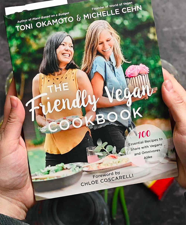 Hands holding The Friendly Vegan Cookbook