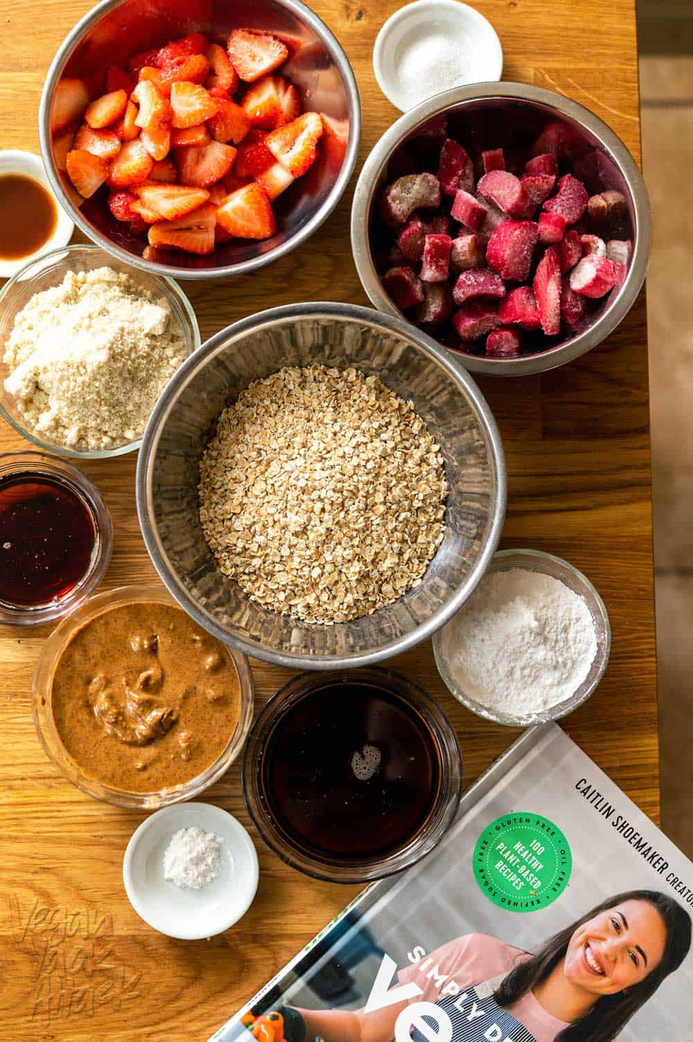 oats, strawberries, rhubarb, maple syrup, and more in small bowls on a cutting board