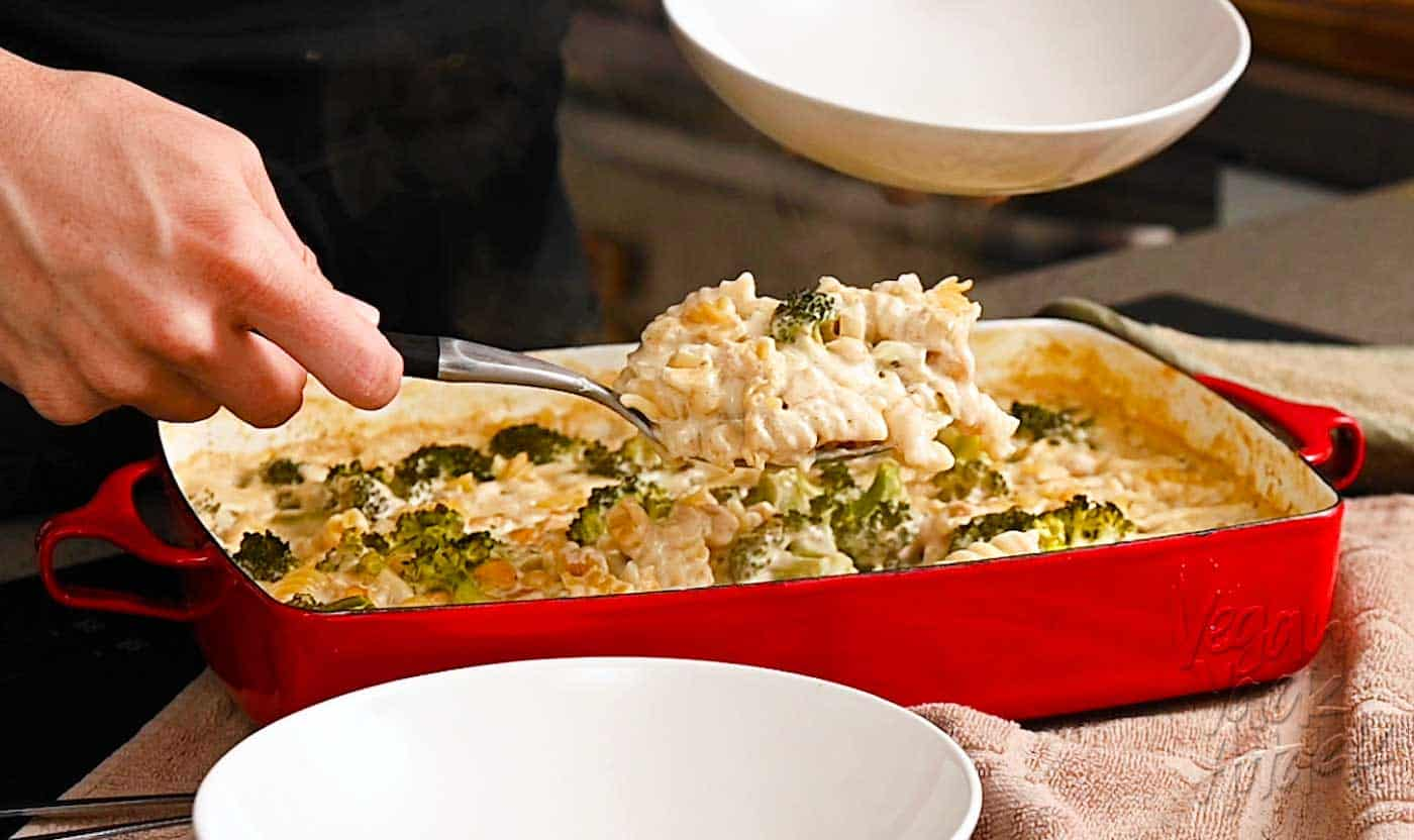 Hand using spoon to scoop pasta casserole into a bowl