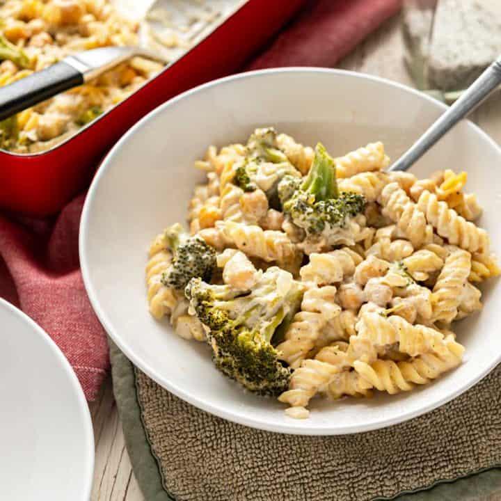 Bowl of No-Boil Broccoli Pasta Bake next to a casserole dish