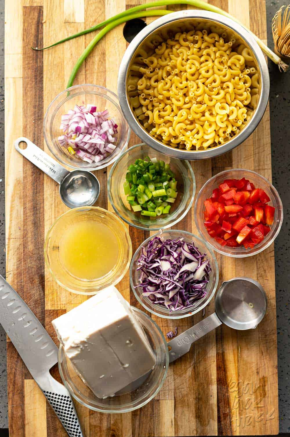 Small bowls with pasta, onions, cabbage, lemon juice and more on a cutting board