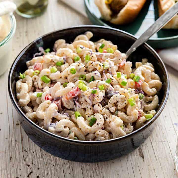 Large bowl of macaroni salad on a white wood background