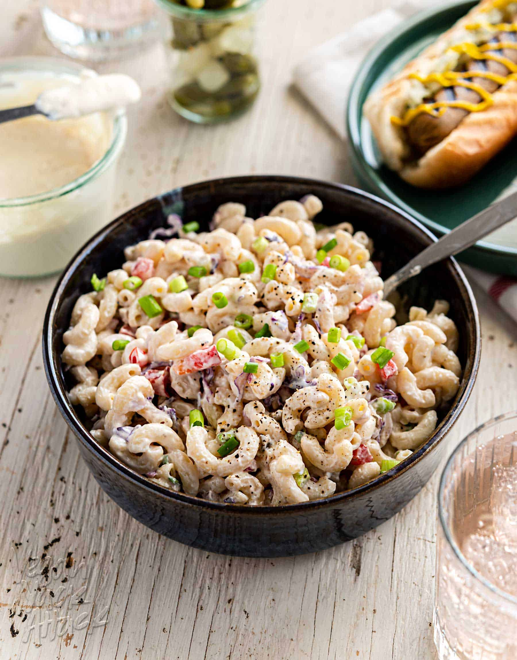 Large bowl of vegan macaroni salad on a white wood background