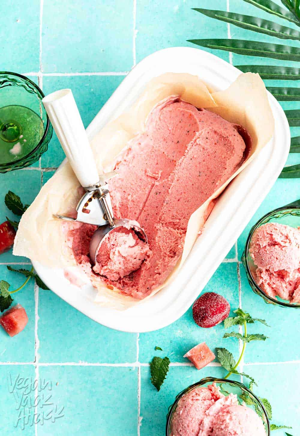Scoops of watermelon sherbet ice cream in green glasses on teal tile with text overlay