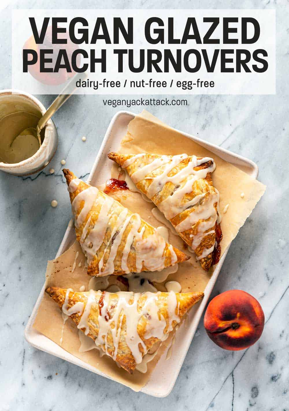 Three vegan peach turnovers on a rectangular plate